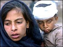 فتاة تحمل شقيقها المصاب في القطاع الباكستاني