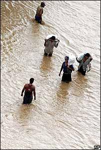 Varios hombres caminan por una zona inundada tras recibir agua y alimentos en La Gomera, Guatemala