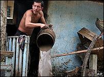 Un hombre saca el agua que inund� su casa en Las Brisas, El Salvador