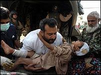 Man carries injured child to US helicopter in Muzaffarabad