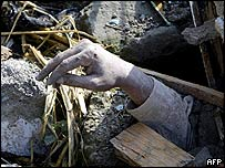 Hand protrudes from crushed house in Muzaffarabad