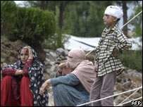 An injured Kashmir boy stands beside his family members outside a tent in Bagh