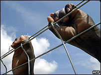 A pair of hands hold onto the fencing around the temporary housing area in the Spanish enclave of Melilla
