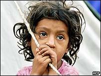 An earthquake victim child waits to get aid at a makeshift shelter in Muzaffarabad