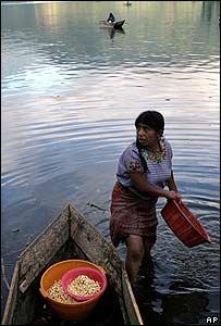 Una indigena maya lava maiz en el lago Atitlan.