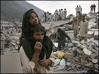Man carries his daughter through the rubble of Balakot, Pakistan