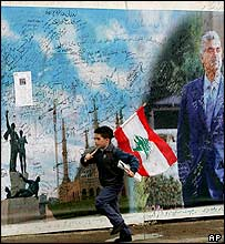 Boy running past poster of Hariri