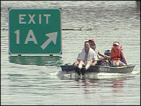 Residents of New Orleans getting around by boat along the main road