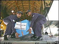 Indian Air Force personnel carry boxes containing relief supplies for quake-affected areas of Pakistan in New Delhi, India