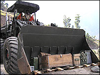 A bulldozer carrying a few household items