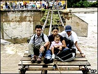 Family are winched to safety along a railway track wrecked by flooding.  Image: AP