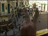 Ayman Nour campaigner makes V-sign from a Cairo balcony