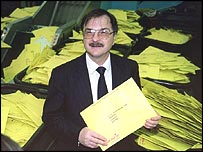Len Cook poses in front of a pile of census forms