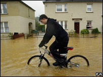 Riding a bike in Hawick floodwaters