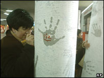 A woman signs a condolence message at Atocha rail station, Madrid