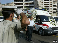 Syrian police officer salutes passing funeral cortege
