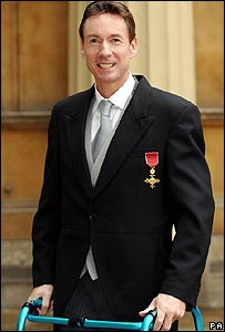 Frank Gardner standing with frame after receiving OBE