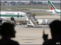 Passengers talk near an Alitalia plane in Rome