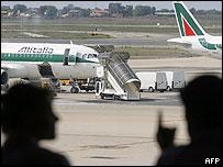 Passengers talk near an Alitalia plane in Rome