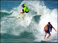 A surfer drops in on another one