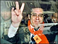 Ayman Nour gives a V-sign from a police vehicle taking him from a Cairo court