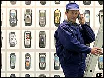 man on ladder in front of poster of mobile phones