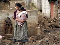 Guatemalan woman among the ruins of a house in Itzapa