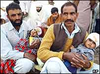 Survivors with injured children wait in Bagh to be evacuated by helicopter