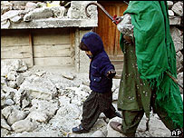 A woman and child walk over rubble in Balakot