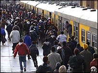 South African commuters run to board a train