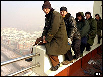 Unpaid migrant construction workers threaten to jump from a rooftop in Shenyang, north China