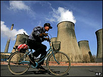 A man cycles past a power plant in Fuxin, Liaoning province