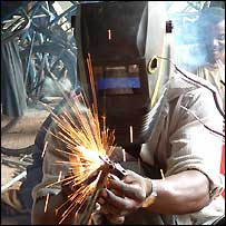 A polio victim welding a giraffe sculpture in Tanzania