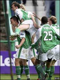 Beuzelin (left) is mobbed by his Hibs team-mates after his second goal of the match