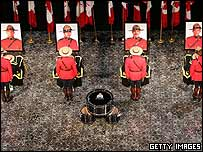 Royal Canadian Mounted Police officers stand guard in front of pictures of the victims