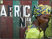A woman walks past a sign reading 'Africa No. 1' at her make shift shop in a market in Bunia, Democratic Republic of Congo