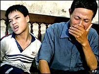 Nguyen Van Quy, 49, weeps while sitting with his son Nguyen Quang Trung, 17, at his house in Hai Phong, Vietnam on July 2004.