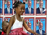 Child walks in front of Mozambique election posters