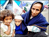 An elderly woman and her grandchildren wait to get relief goods at a refugee camp in Muzaffarabad.