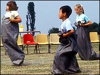 Primary school children take part in a sack race on sports day