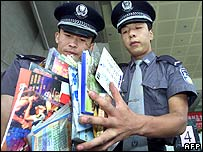 Two Chinese policemen holding pirated CDs