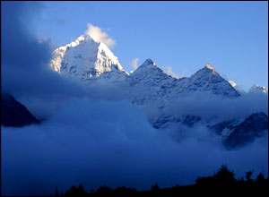 Photo of mountains in the clouds, predominant colour is blue