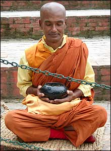 Photo of a Buddhist monk in orange robes with his begging bowl