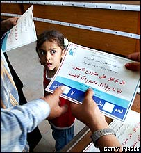 Young girl watches ballots change hands in polling office