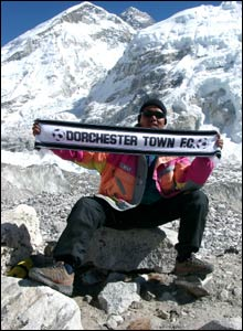 Photo of Sherpa guide, Nuru holding a football scarf against a mountain backdrop