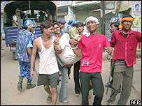 An injured man being carried in Mau