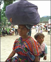 Woman carrying belongings on head and baby on back, Antigua, Guatemala