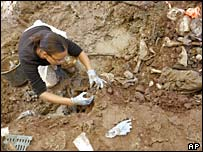 A forensic scientist examines a mass grave in Liplje