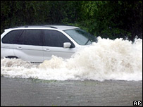 A car navigates through floodwater from Tropical Storm Wilma in Kingston, Jamaica