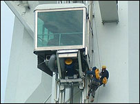 Workmen try to fix the glass lift after it breaks down on the tower's opening day